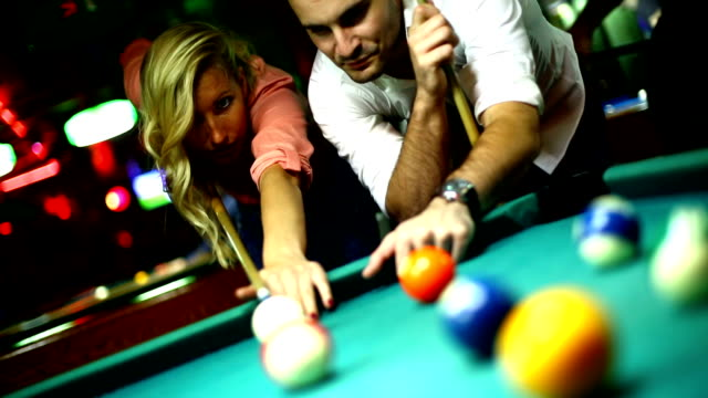 Gruppe von Freunden shooting pool an einem Abend.