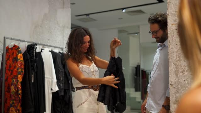 衣料品店で買い物をする友人のグループ - ハンガー点の映像素材/bロール