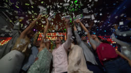 Group of friends shouting new year countdown for 2020 at a bar all excited hugging