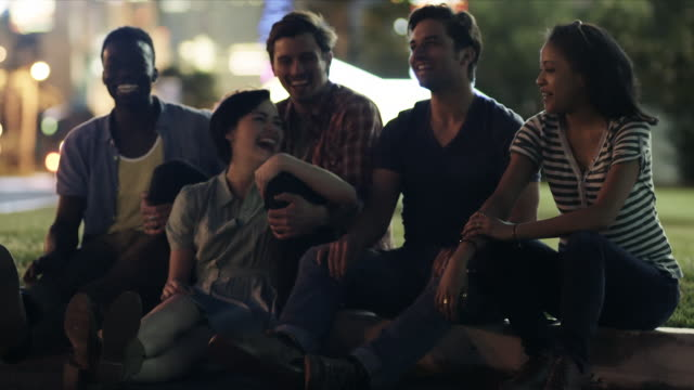 Group of friends sit and laugh on curb outside Vegas motel late at night