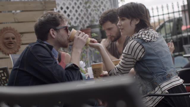 vídeos y material grabado en eventos de stock de group of friends sit and talk over coffee at outdoor caf_ - guay