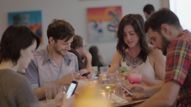 Group of friends sit around restaurant table distracted by smartphones