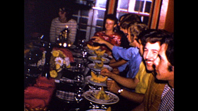 group of friends sit around the table and begin eating at a dinner party. - friendship stock videos & royalty-free footage