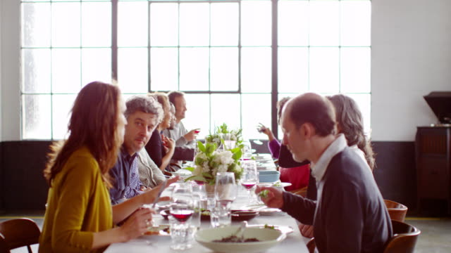 MS group of friends sitting at dinner party in loft eating dinner