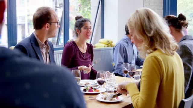 vídeos de stock, filmes e b-roll de ms r/f group of friends sitting at table in restaurant eating dinner - garfo