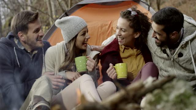 vídeos de stock e filmes b-roll de group of friends sitting by campfire - fogueira de acampamento