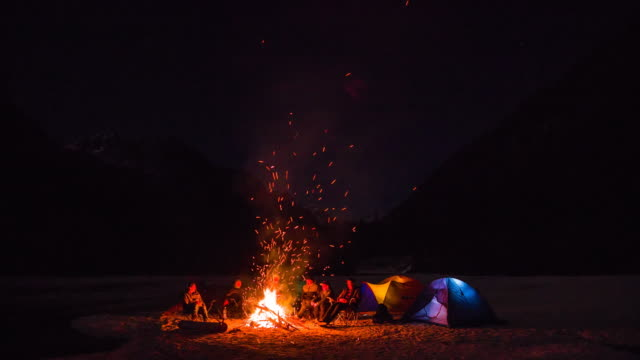 group of friends sitting by the campfire - camping stock videos & royalty-free footage