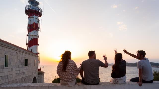 vídeos de stock e filmes b-roll de ws group of friends sitting in front of lighthouse overlooking the mediterranean sea at sunset - farol estrutura construída