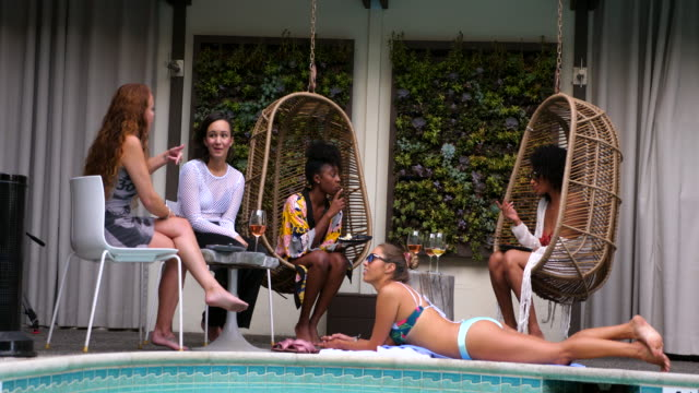ms group of friends sitting on edge of hotel pool during party - amicizia tra donne video stock e b–roll