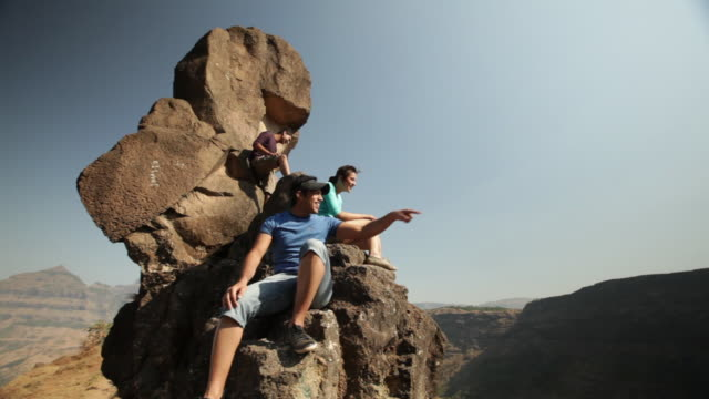 group of friends sitting on the cliff of a mountain - teenage boys stock videos & royalty-free footage