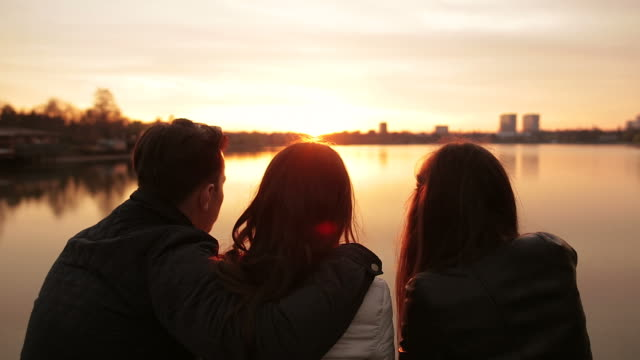group of friends sitting on the edge of the lake and relaxing at sunset. - arm around stock videos & royalty-free footage