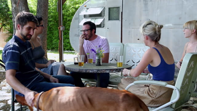 ms group of friends sitting outside at table having drinks laughing man petting dog - camper trailer stock videos and b-roll footage