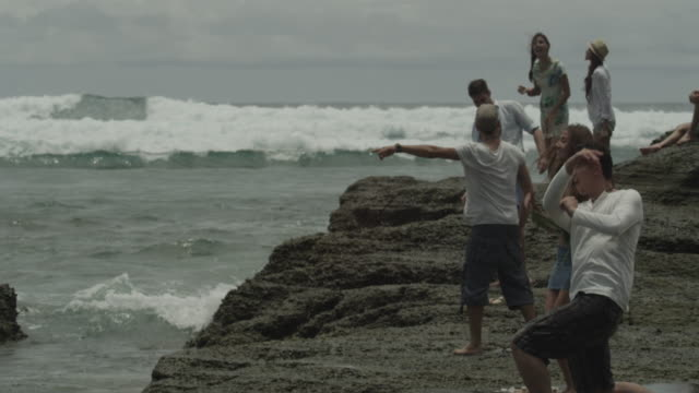 stockvideo's en b-roll-footage met a group of friends skimming stones by the shore. - huppelen