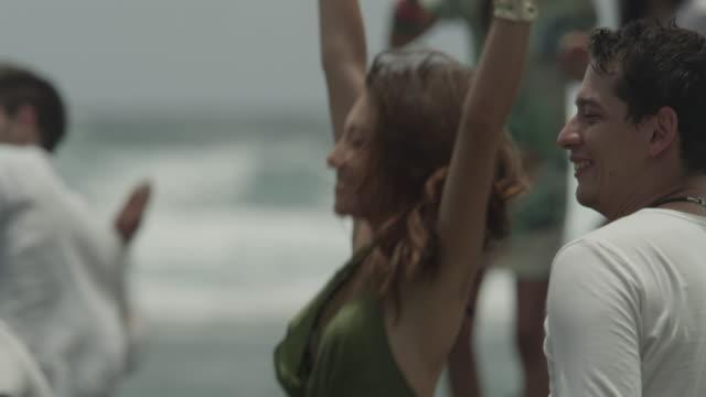 vidéos et rushes de a group of friends skimming stones by the shore. - 25 29 ans