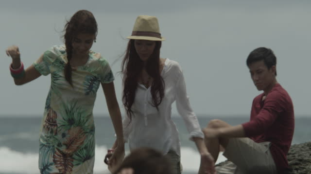 stockvideo's en b-roll-footage met a group of friends skimming stones by the shore. - hemden en shirts