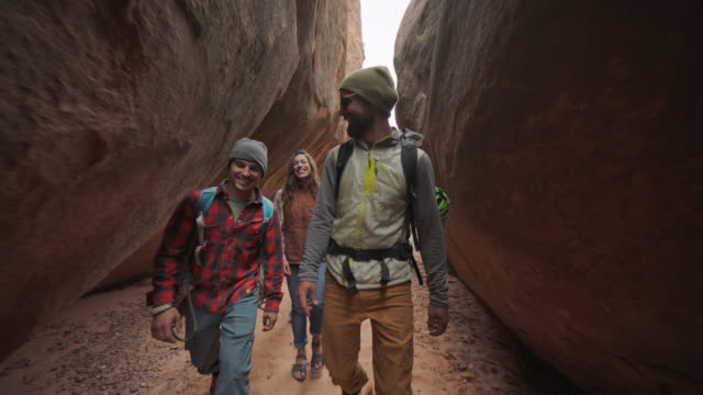 SLO MO. Group of friends smile as they walk through sandstone slot canyon on Moab adventure.