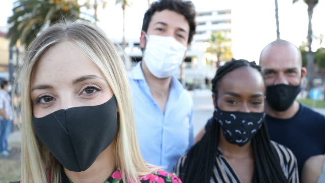 group of friends smiling to the camera wearing protective face masks - group of people stock videos & royalty-free footage