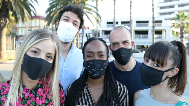 group of friends smiling to the camera wearing protective face masks - illness prevention stock videos & royalty-free footage