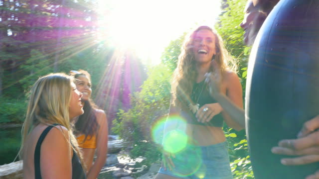 ms group of friends standing on riverbank laughing after swimming on summer afternoon - quattro persone video stock e b–roll