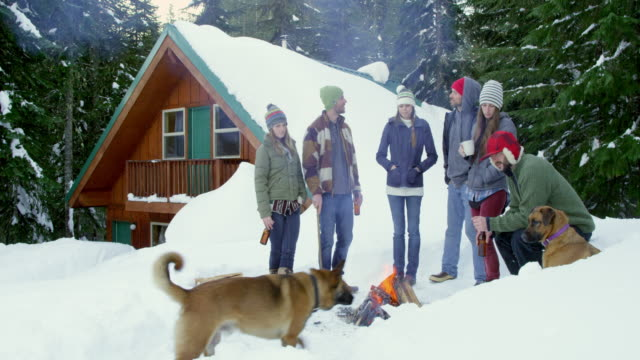 MS group of friends standing with dogs around fire in front of cabin in snow.