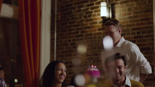 Group of friends surprise woman with birthday cake in gourmet restaurant