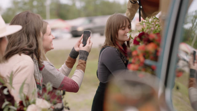 group of friends take photos and shop together at a mobile flower truck - real life stock videos & royalty-free footage