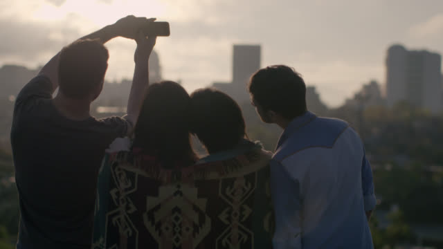 Group of friends take selfie on rooftop overlooking city skyline