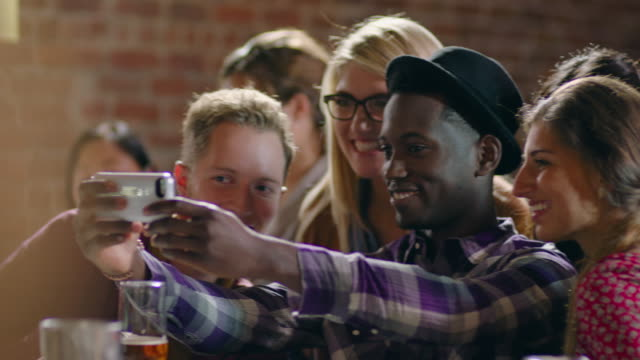Group of friends take selfie with smartphone in crowded bar