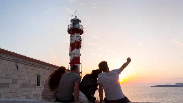 WS group of friends taking photos in front of lighthouse overlooking the mediterranean sea at sunset