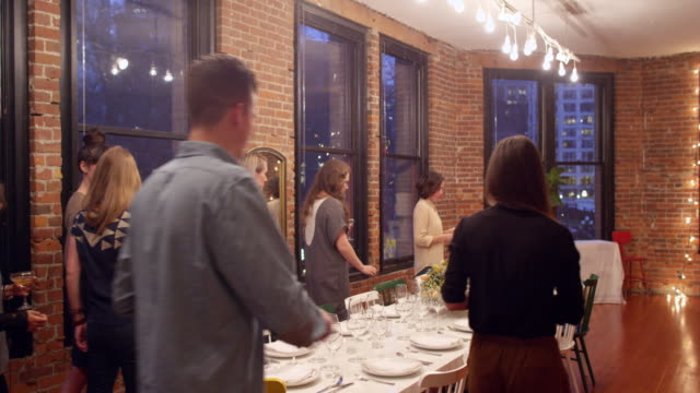 ms group of friends taking seats at table during dinner party in loft - arrival stock videos & royalty-free footage