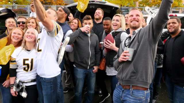 MS Group of friends taking selfie at tailgating party in stadium parking lot before football game