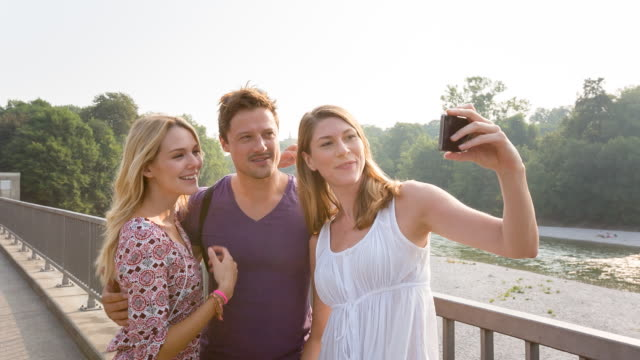 group of friends taking selfie photo by river - technophile stock videos & royalty-free footage