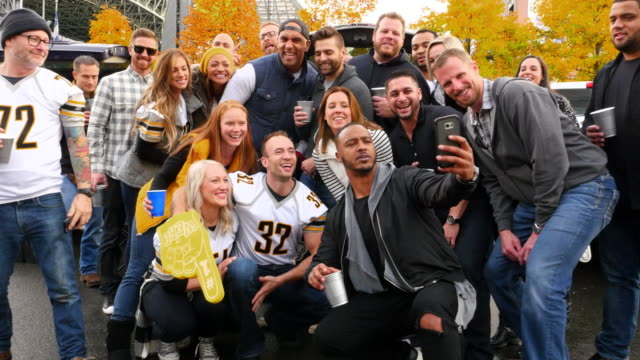 MS ZI Group of friends taking selfie together at tailgating party before football game