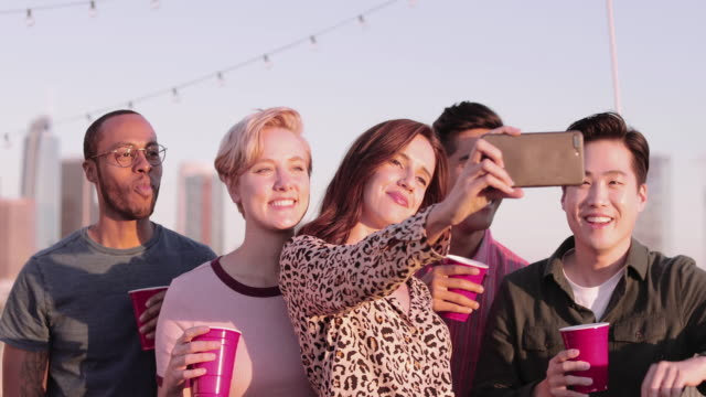 group of friends taking selfie with city skyline in background - five people stock videos & royalty-free footage