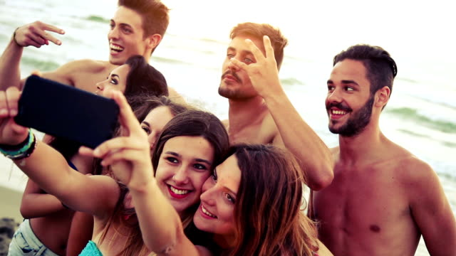 Group of friends taking selfies on the beach