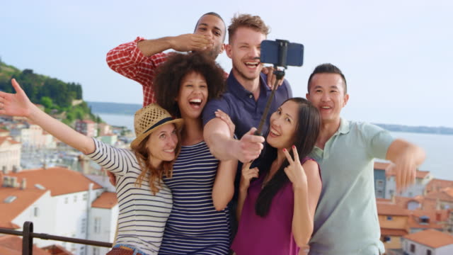 A group of friends taking selfies using a selfie stick on a walkway overlooking a nice coastal town