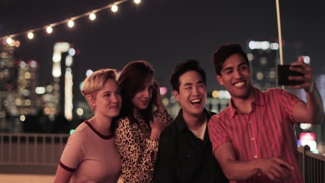 group of friends taking selfies with city skyline at night - 自分撮り点の映像素材/bロール