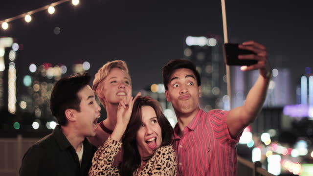 group of friends taking selfies with city skyline at night - patio stock videos & royalty-free footage