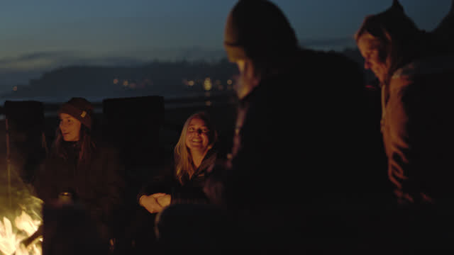 vídeos y material grabado en eventos de stock de group of friends talk and laugh around a beachside campfire at dusk. - fire natural phenomenon