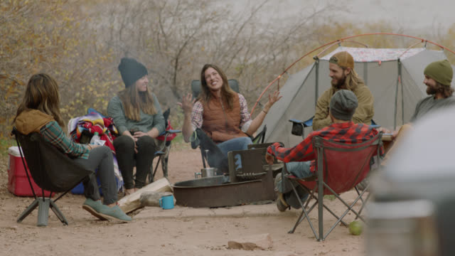Group of friends talk and laugh around campground fire pit.