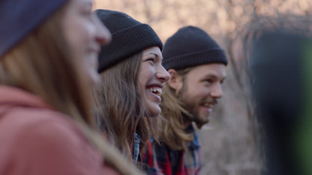 group of friends talk and laugh while sipping coffee by fire pit on weekend camping trip. - woolly hat stock videos and b-roll footage