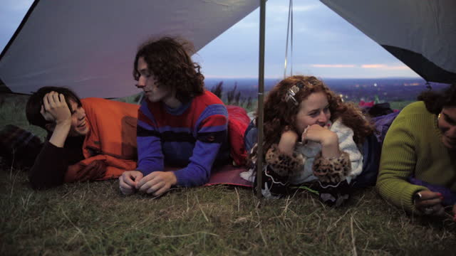 group of friends talking and laughing and lying together in a tent at sunset - east sussex stock videos & royalty-free footage