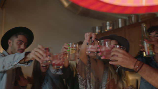 group of friends throwing a wild house party raise their glasses and cheers their drinks and toast to their friend checking his smartphone on the couch. - drinking stock videos & royalty-free footage