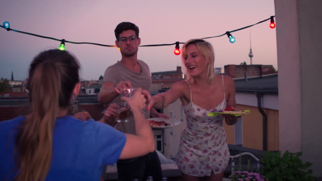 A group of friends toast on an urban rooftop