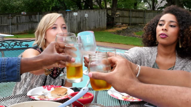 ms zo group of friends toasting drinks while dining together at table in backyard on summer evening - honour stock videos & royalty-free footage
