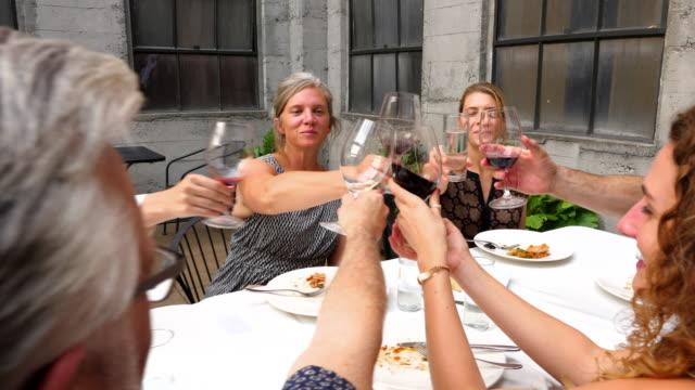 pan group of friends toasting with wine glasses during dinner party on restaurant patio - 40 44 anni video stock e b–roll