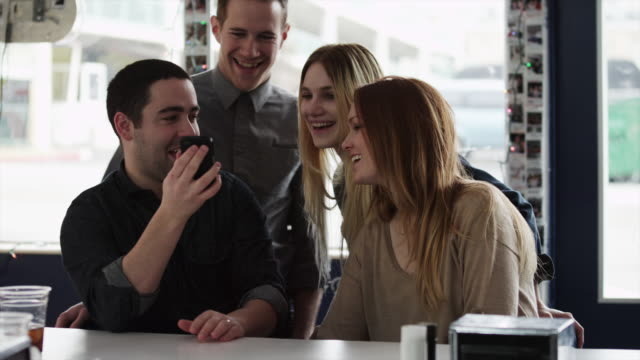 ms group of friends using cell phone together / provo,utah,usa - provo bildbanksvideor och videomaterial från bakom kulisserna
