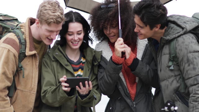 Group of friends using smartphone outdoors in rain