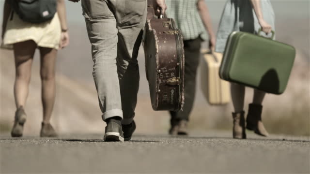 Group of friends walk away down desert road carrying luggage