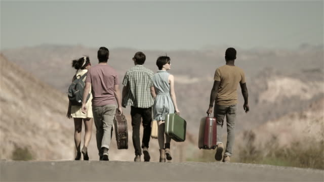 Group of friends walk down scenic desert road carrying luggage